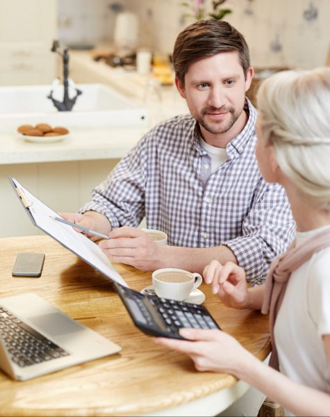 Confident enterprising young couple filing tax return and discussing document while checking financial figures and drinking coffee in domestic kitchen