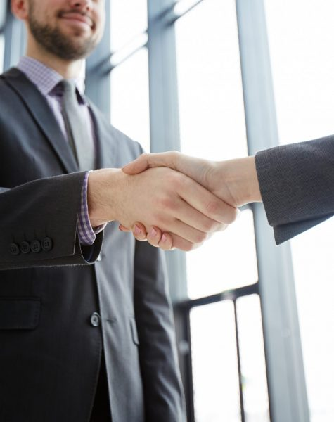 Handshake of successful business partners in formalwear after making agreement