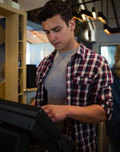 Male owner using cash register at restaurant