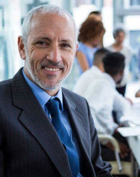 Portrait of happy businessman sitting in office