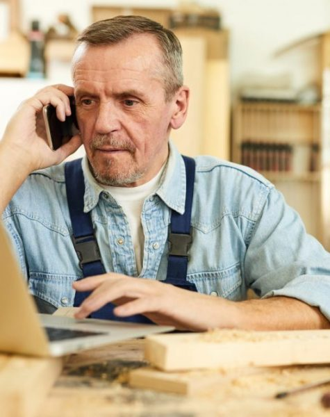Portrait of modern senior carpenter speaking by phone and using laptop while working in joinery, copy space