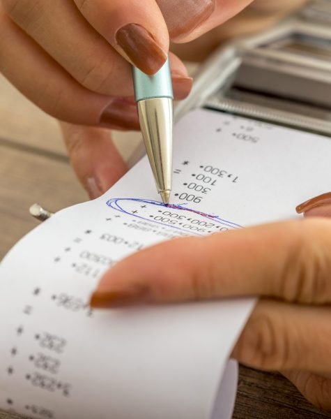 Tax and accounting business concept - closeup of female hands working with adding machine and printout circling important figures wit a pen.